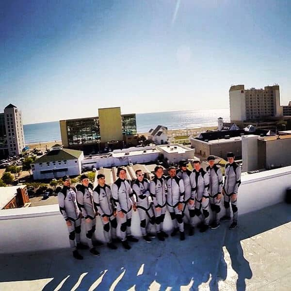 A photo of the instructors in their flight suits on top of the wind tunnel.