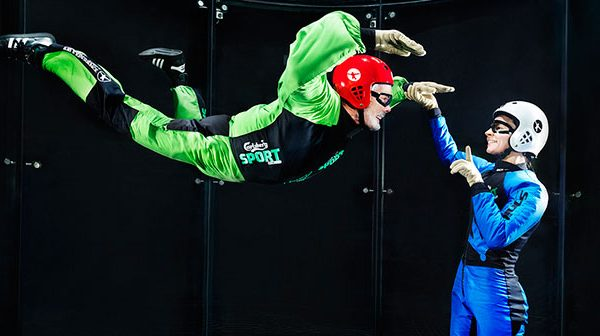 Instructor working with a first time flyer in a wind tunnel